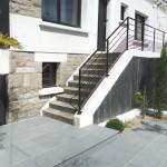 L'entrée extérieure d'une maison de ville avec un brise vue en ardoise