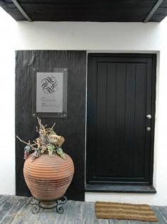 Une entrée de maison avec une porte noire et une décoration en ardoise