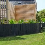 Piquets de schiste ardoise mis bord à bord dans un jardin pour délimiter la pelouse des plantes